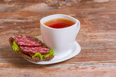 Breakfast with salami sandwich and cup of tea Royalty Free Stock Photos