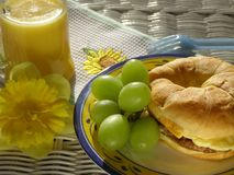 Breakfast Sandwich. With sausage, egg and cheese on a croissant with green grapes and orange juice Stock Photography