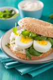 Breakfast sandwich on bagel with egg cream cheese arugula Stock Image