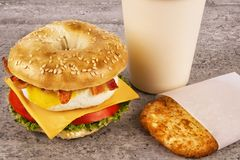 Breakfast sandwich with coffee and hash brown on concrete table. Bagle, egg, cheese and bacon stock images