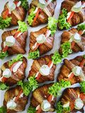 Breakfast sandwiches with mini croissants, smoked salmon slices and parsley on patterned background. Croissants with red Stock Photos
