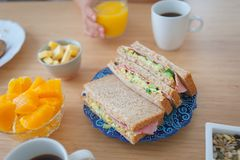 Breakfast with sandwiches, oranges, fruits, coffee, juice cheese and nuts. Morning meal, breakfast with sandwiches and other side dishes, nuts, oranges, juice Stock Photo