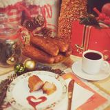 Christmas breakfast. Sausages in batter with ketchup and a cup of black coffee  against the backdrop of the banks and gold and green Christmas balls and also Royalty Free Stock Photo