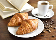 Breakfast scene with fresh croissants. Coffee cup, coffee beans and open book. Relaxation morning scene with hot coffee Stock Photo