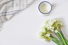 Breakfast scene with mug of milk, tea towel and bouquet of narcissus, daffodil flowers on white table background. Spring. Composition, Easter concept. Flat lay Royalty Free Stock Photo