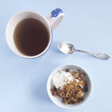 Breakfast scene. With tea and yogurt with muesli Stock Image