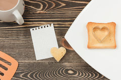 Breakfast scene with toast, cup on wooden table. Royalty Free Stock Photography