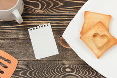 Breakfast scene with toast, cup on wooden table. Top view Royalty Free Stock Photo