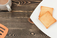Breakfast scene with toast, cup on wooden table. Top view Stock Images