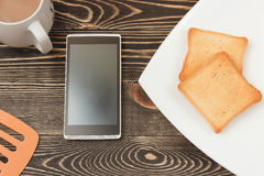 Breakfast scene with toast, phone, cup on wooden table. Royalty Free Stock Images
