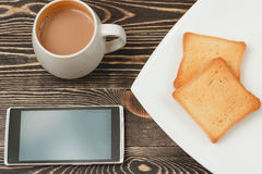 Breakfast scene with toast, phone, cup on wooden table. Top view Royalty Free Stock Photo
