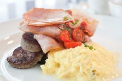 Bacon, sausage and eggs breakfast. Breakfast of scrambled eggs, bacon, sausage and cherry tomatoes served on a white plate Royalty Free Stock Photo