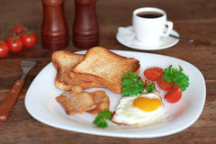 Breakfast with scrambled eggs. Breakfast with scrambled eggs, bacon, toast and fresh vegetables Stock Photography