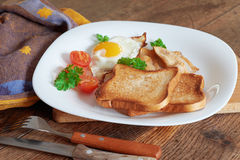 Breakfast with scrambled eggs. Breakfast with scrambled eggs, bacon, toast and fresh vegetables Stock Photos