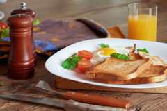 Breakfast with scrambled eggs. Breakfast with scrambled eggs, bacon, toast and fresh vegetables Stock Photo