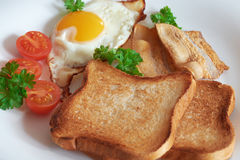 Breakfast with scrambled eggs. Breakfast with scrambled eggs, bacon, toast and fresh vegetables Stock Image