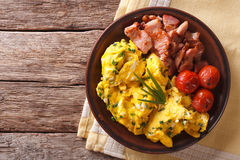 Breakfast is scrambled eggs with chives, fried bacon closeup. Ho Royalty Free Stock Photos