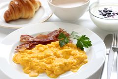 Breakfast. With scrambled eggs, crispy bacon, croissant,yogurt and cafe au lait Royalty Free Stock Image