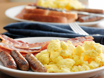 Breakfast - scrambled eggs, sausage, and bacon Stock Photos