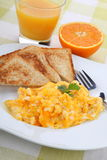 Breakfast with scrambled eggs, toasts, juice and coffee Royalty Free Stock Image