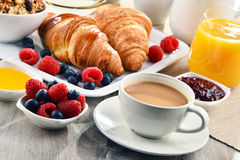 Breakfast served with coffee, juice, croissants and fruits stock photography