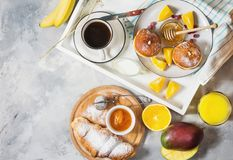 Breakfast served with coffee, orange juice, croissants, donuts and fruits on white tray stock photo