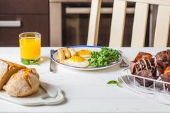 Breakfast served with fried eggs, salad, muffins and orange juice on white wooden table. royalty free stock image