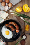 Breakfast served with scrambled eggs, fried sausages, yellow tomatoes and green onions. Breakfast served with scrambled eggs, fried sausages, yellow tomatoes stock photography