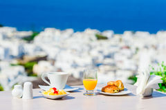 Breakfast served table by the sea. Perfect luxury breakfast table outdoors. Amazing caldera view on Mykonos, Greece Royalty Free Stock Image