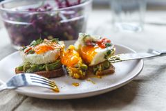 Breakfast served of two toasts with avocado, fried eggs with vegetables and herbs on a rustic tablecloth background. View from. Above. Healthy and nutritious stock photography