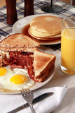 Breakfast Serving of Bacon and Eggs. Bacon and eggs breakfast serving including orange juice, toast, and pancakes Royalty Free Stock Photos