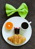 Breakfast serving funny face on the plate (jam, croissant, orange) Stock Image