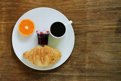 Breakfast serving funny face on the plate (jam, croissant, orange) Stock Photo