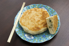Breakfast sesame pancake. A breakfast sesame pancake with green onions inside on a dish with chopsticks Stock Photography