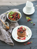 Breakfast set. Buckwheat pancakes with fresh berries and honey on rustic plate over black wooden table. Stock Image