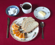 Breakfast set with coffee, bread, butter and orange wedges on a red tablecloth Stock Photos