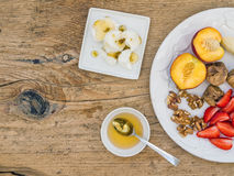 Breakfast set with fresh strawberry, banana, peach, dry figs, wa. Lnuts, soft goat cheese and honey on a rough wooden surface Stock Images