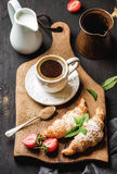 Breakfast set. Freshly baked croissants with strawberry, mint leaves and cup of coffee on wooden board over dark Stock Images