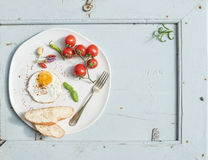 Breakfast set. Fried egg, bread slices, cherry tomatoes, hot peppers and herbs on white ceramic plate over light blue Stock Photo