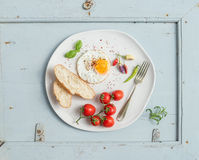 Breakfast set. Fried egg, bread slices, cherry tomatoes, hot peppers and herbs on white ceramic plate over light blue Royalty Free Stock Photography