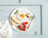 Breakfast set. Fried egg, bread slices, cherry tomatoes, hot peppers and herbs on white ceramic plate over light blue Stock Photos