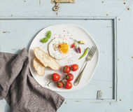 Breakfast set. Fried egg, bread slices, cherry tomatoes, hot peppers and herbs on white ceramic plate over light blue Royalty Free Stock Images
