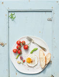 Breakfast set. Fried egg, bread slices, cherry tomatoes, hot peppers and herbs Royalty Free Stock Photo