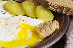 Breakfast set. Of fried eggs with marinated cucumber and rye bread. Rustic style. Stock Photos