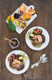 Breakfast set. Homemade zuccini pancakes with fresh plum, tangerine, grapes, figs and honey in white ceramic plates over Royalty Free Stock Images