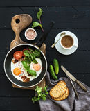 Breakfast set. Pan of fried eggs, bacon, tomatoes with bread, mangold and cucumbers, coffee on rustic wooden serving Stock Photo