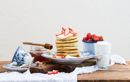 Breakfast set. Pancake tower with fresh strawberries, sour cream and honey on a porcelain plate over rustic wooden table. Blue enamel cup full of berries Stock Photos