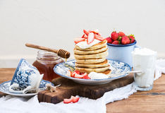 Breakfast set. Pancakes with fresh strawberries, sour cream and honey on a porcelain plate over rustic wooden table. Breakfast set. Pancaks with fresh Stock Image