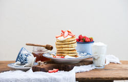 Breakfast set. Pancakes with fresh strawberries, sour cream and honey on a porcelain plate over rustic wooden table. Breakfast set. Pancaks with fresh Royalty Free Stock Image