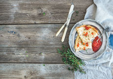 Breakfast set. Thin crepes with red caviar on rustic metal plate, fresh thyme and vintage dinnerware over a rough wood background. Royalty Free Stock Photos